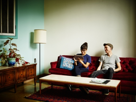 Smiling couple sitting on couch in living room working on digital tablet