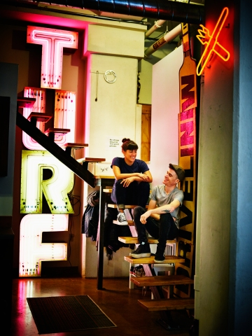 Neon artists sitting on stairs in industrial loft surrounded by neon signs
